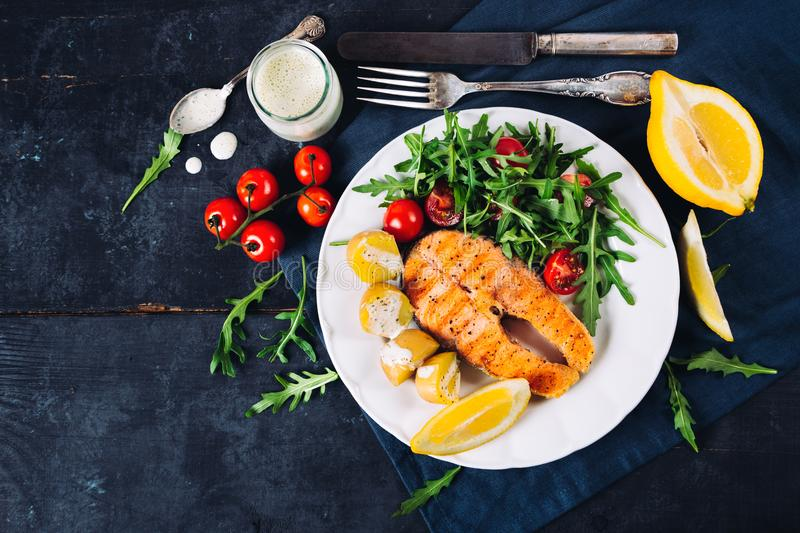 Grilled salmon with arugula and cherry tomato salad and potatoes. Slice of grilled salmon garnished with cooked potatoes, arugula and cherry tomato salad royalty free stock images