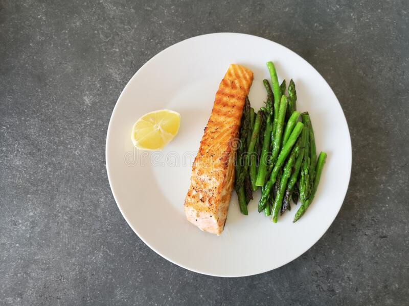 Grilled salmon with asparagus and lemon royalty free stock images
