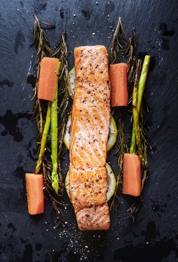 Grilled Salmon baked fillet steak, with lemon, Asparagus, Rosemary and Carrot royalty free stock images