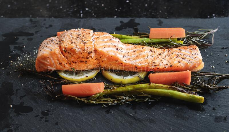 Grilled Salmon baked fillet steak, with lemon, Asparagus, Rosemary and Carrot royalty free stock photo