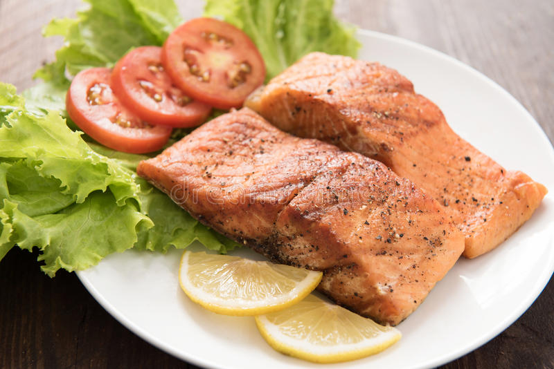Grilled salmon fillet cooked BBQ and served with fresh herbs and. Lemon royalty free stock images