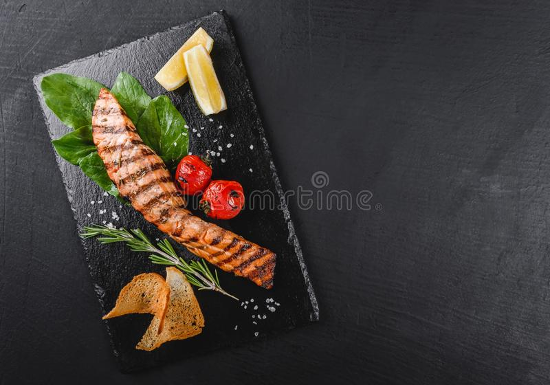 Grilled salmon fillet garnished with spinach, lemon, herbs on plate over wooden background. Hot fish dish, top view.  stock images