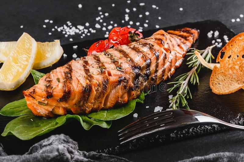Grilled salmon fillet garnished with spinach, lemon, herbs on on stone board on black table surface. Hot fish dish.  stock photography