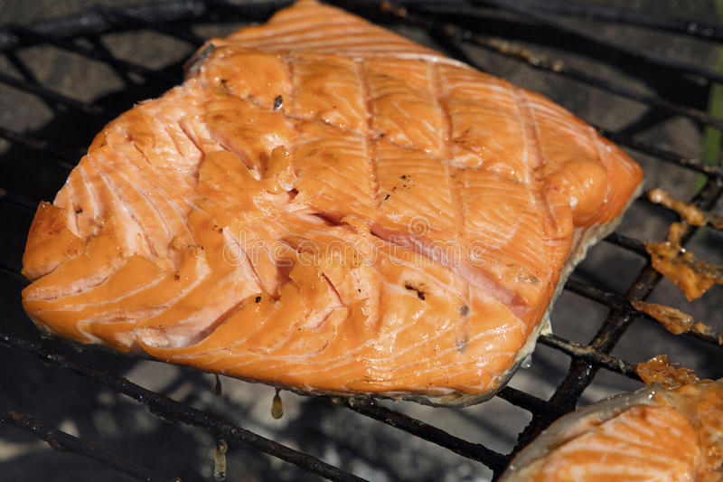 Grilled salmon fish fillet barbecue grill cooking. One grilled salmon fish fillet barbecue cooking prepared on bbq grill, close up royalty free stock image