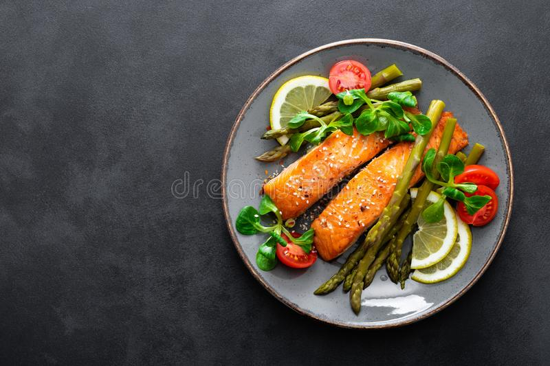 Grilled salmon fish steak, asparagus, tomato and corn salad on plate. Healthy dish for lunch royalty free stock photo