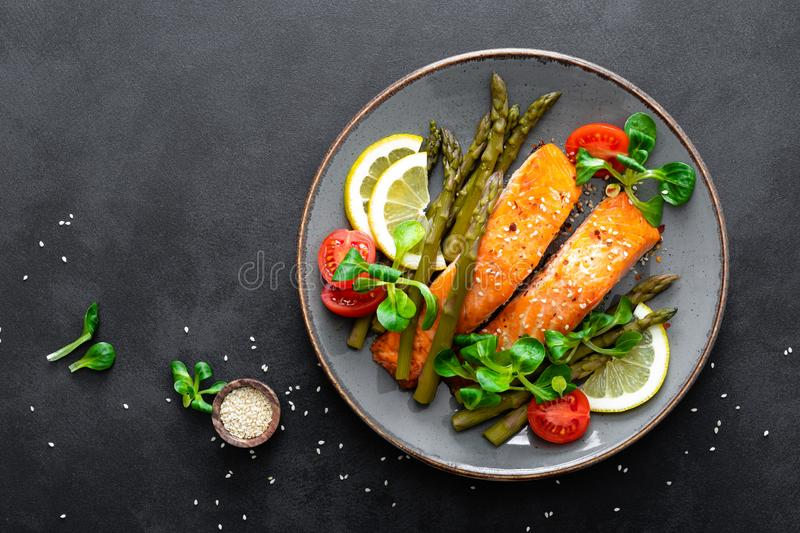 Grilled salmon fish steak, asparagus, tomato and corn salad on plate. Healthy dish for lunch royalty free stock images