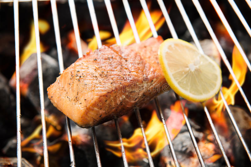 Grilled salmon with lemon on the flaming.  stock photo