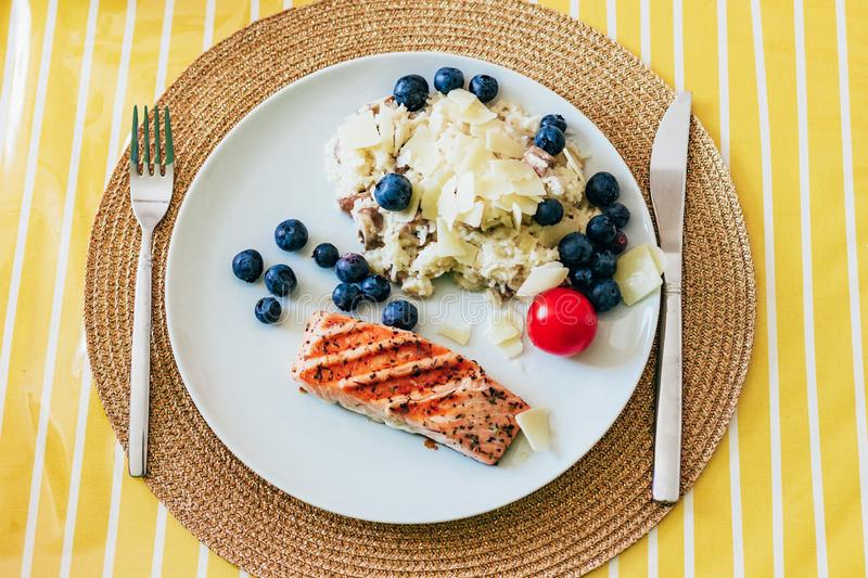 Grilled salmon and risotto with blueberry stock photos