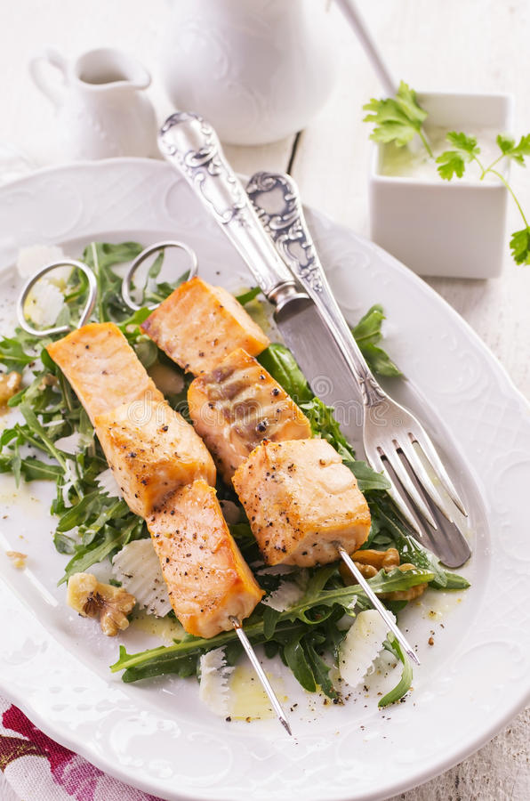 Grilled Salmon with Rucola Salad. As closeup on a white plate stock images