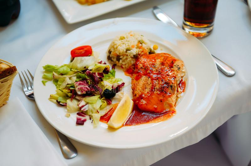 Grilled salmon with sauce, rice and vegetables on a white plate. Gala dinner in the restaurant. Banquet service stock photography