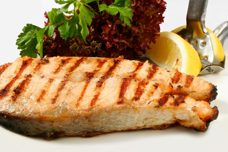 Grilled salmon steak. With salad and lemon stock photos
