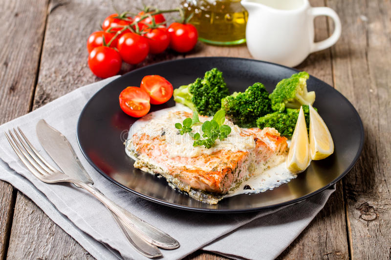 Grilled Salmon Steak with Cream sauce. Grilled Salmon Steak with Broccoli, Cream sauce and Lemon Wedges on wooden background stock photo