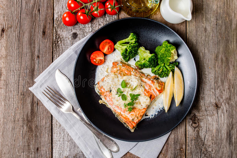 Grilled Salmon Steak with Cream sauce. Grilled Salmon Steak with Broccoli, Cream sauce and Lemon Wedges on wooden background, top view stock photography
