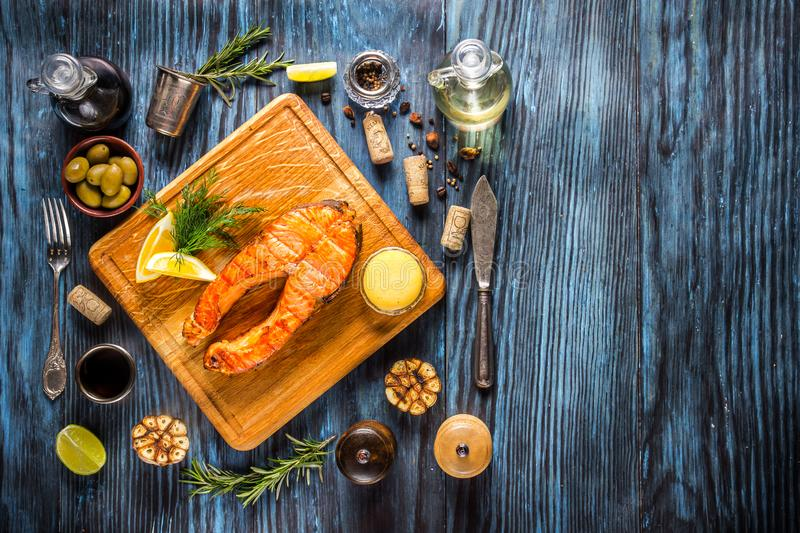 Grilled salmon steak with lemon on rustic wooden background royalty free stock photography