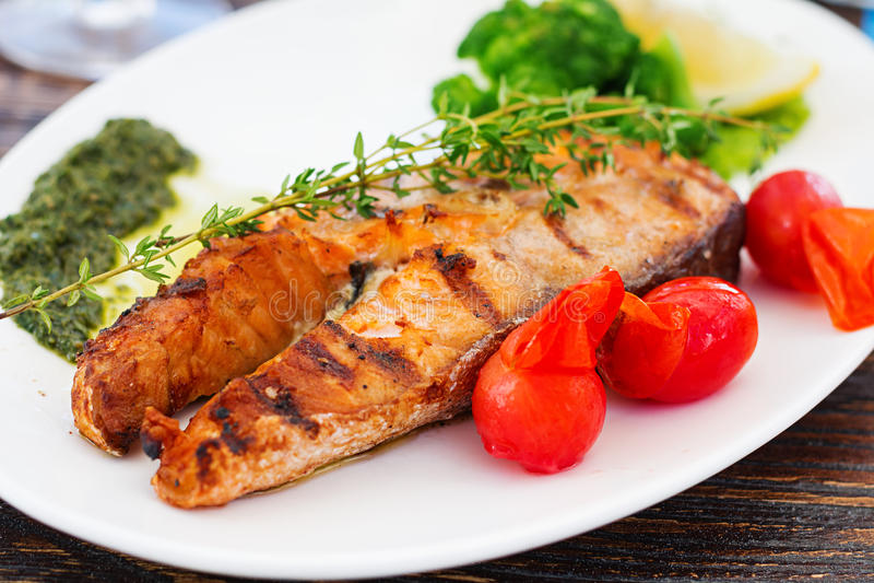 Grilled salmon steak with pesto sauce stock photo
