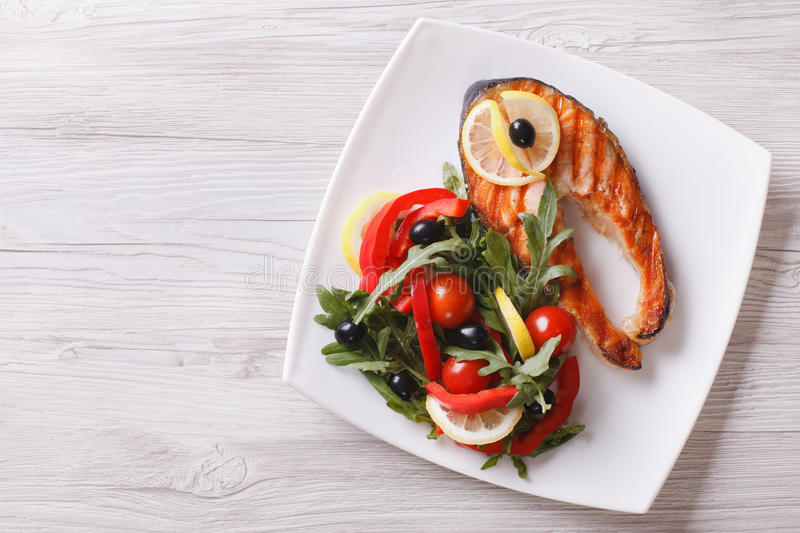 Grilled salmon steak and salad on a plate. horizontal top view. Grilled red fish salmon and a salad on a plate. horizontal view from above royalty free stock image
