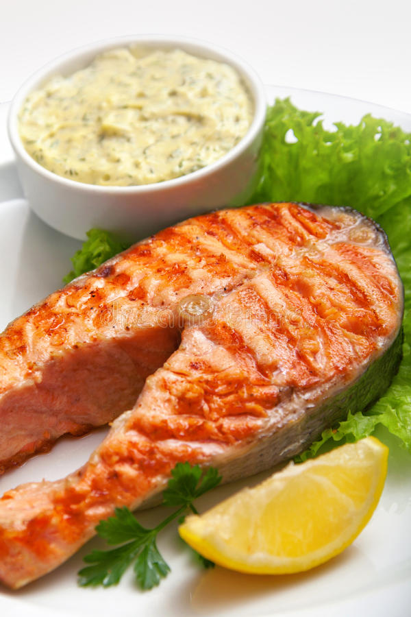 Grilled salmon steak with sauce, parsley and lemon stock image