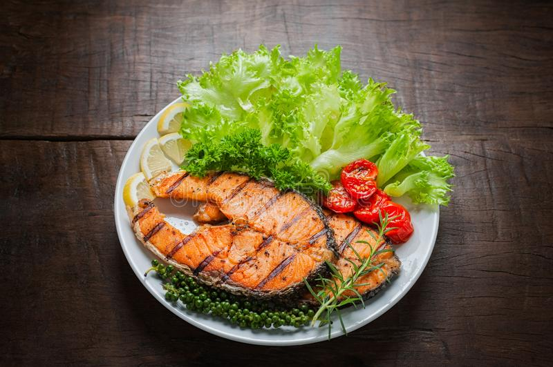Grilled salmon steak served with grilled tomatoes, salad, lemon sliced, pepper seeds, rosemary, parsley stock photo