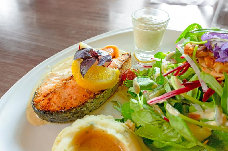 Grilled salmon steak sliced on white plate with mixed vegetable salad, mashed potatoes and topping in a glass, food in dish. On wooden table and copy space stock image