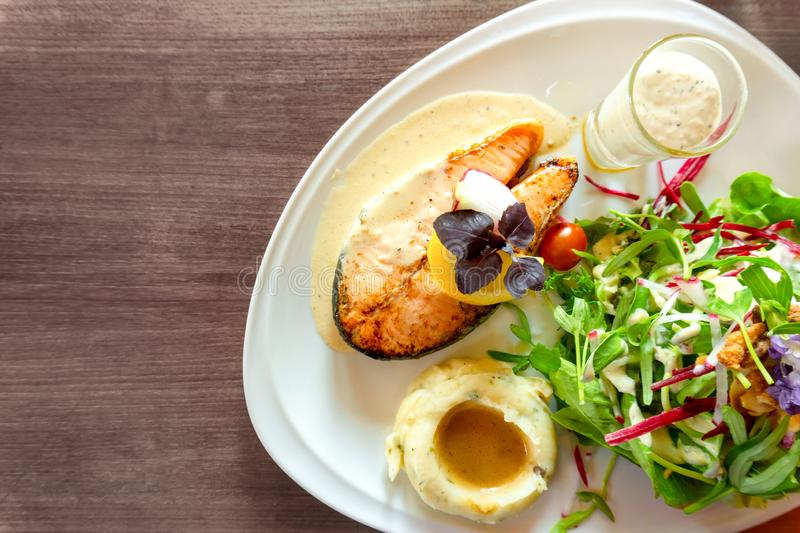 Grilled salmon steak sliced on white plate with mixed vegetable salad, mashed potatoes and topping in a glass, food in dish. On wooden table, top view and copy stock photo