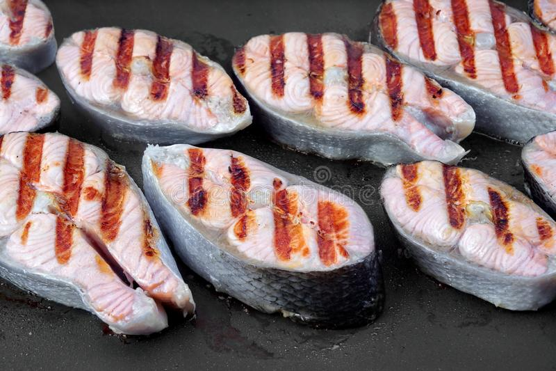 Grilled Salmon Steaks On The Hot Pan. Grilled Salmon Steaks On The Black Hot Pan Close-up stock photography