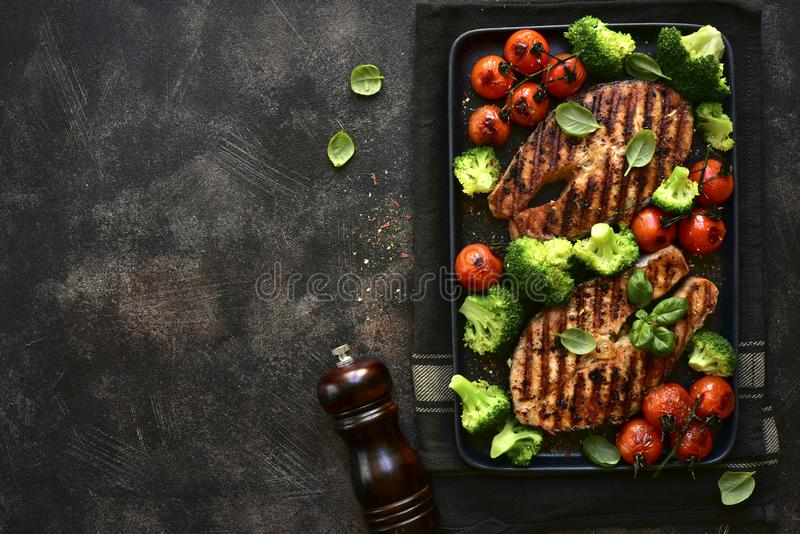 Grilled salmon steaks with vegetables.Top view with copy space royalty free stock photo