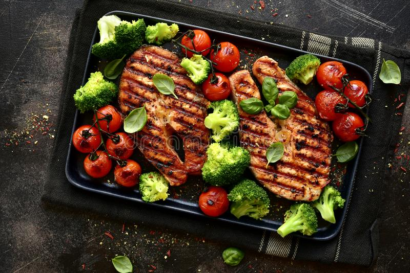 Grilled salmon steaks with vegetables.Top view with copy space stock image