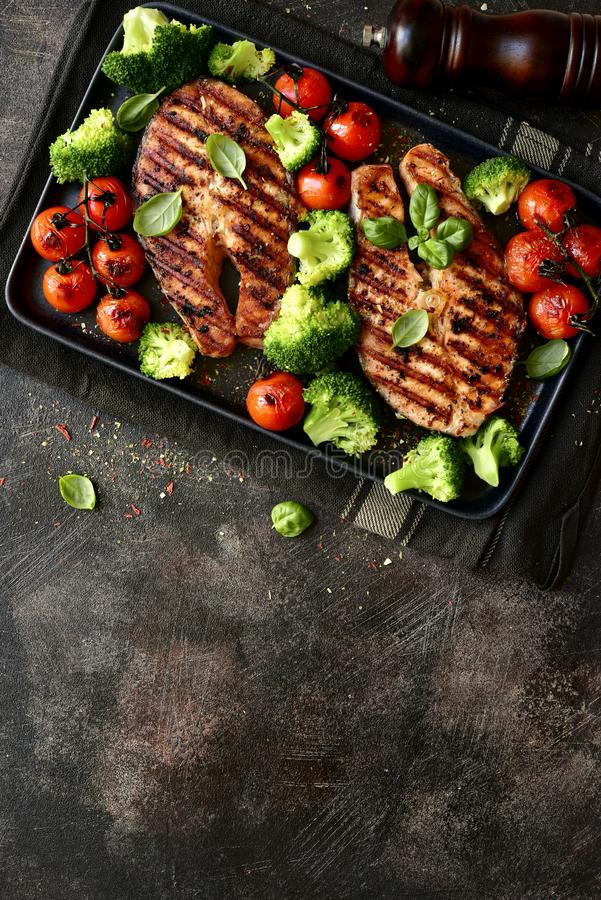 Grilled salmon steaks with vegetables.Top view with copy space royalty free stock photography