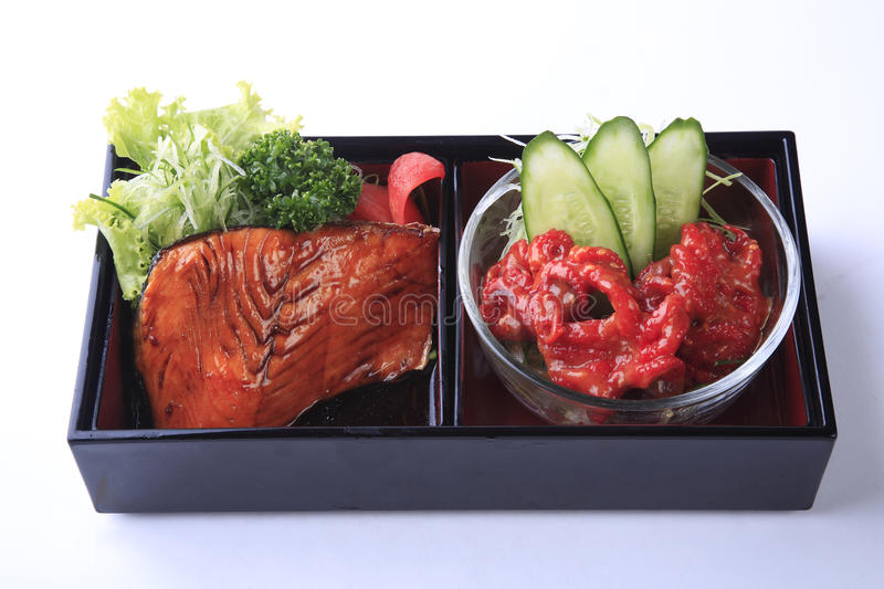 Grilled salmon teriyaki with spicy tentacles in bento isolated o royalty free stock images