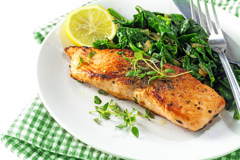 Grilled salmon with thyme, lemon and spinach, vegetarian low car. Grilled salmon with thyme, lemon and spinach on a plate, vegetarian low carb dish, green white stock image