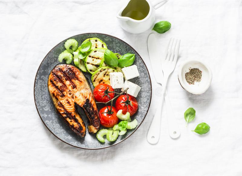 Grilled salmon, zucchini, baked cherry tomatoes and feta cheese - healthy balanced meal on light background stock photography