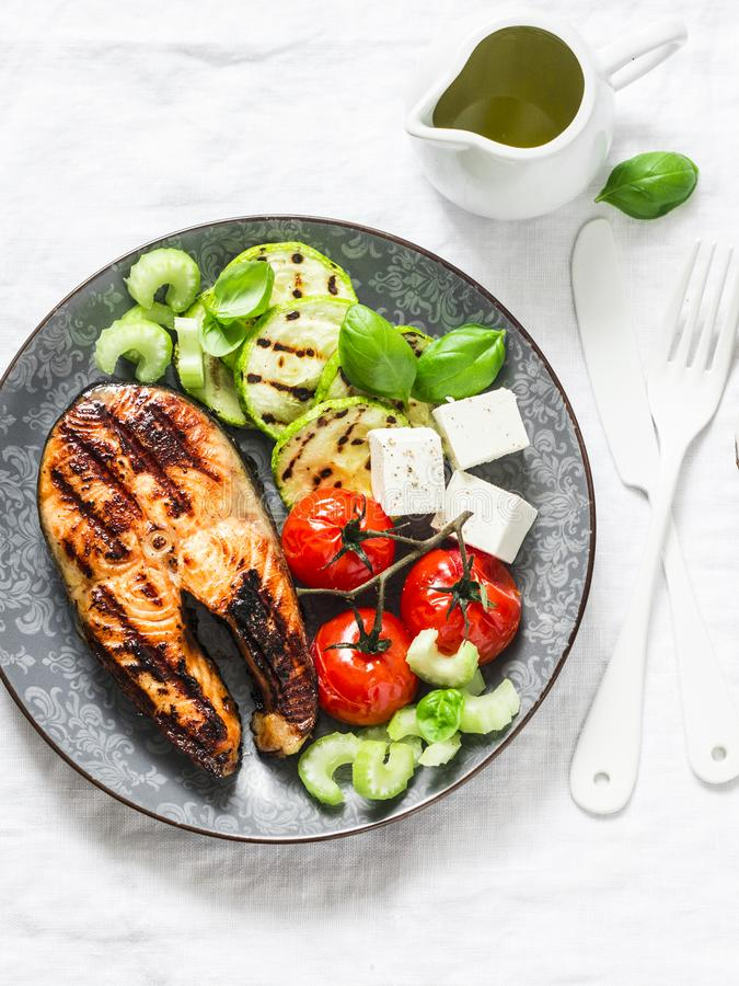 Grilled salmon, zucchini, baked cherry tomatoes and feta cheese - healthy balanced meal on light background stock photos