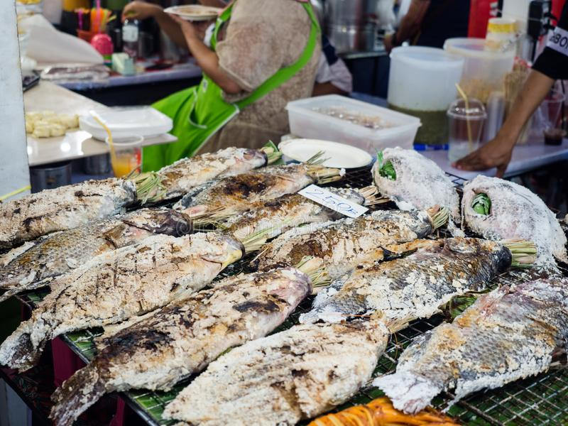 Grilled salt crusted whole body fish fill Thai herbs inside in street food, Thailand.  royalty free stock photos