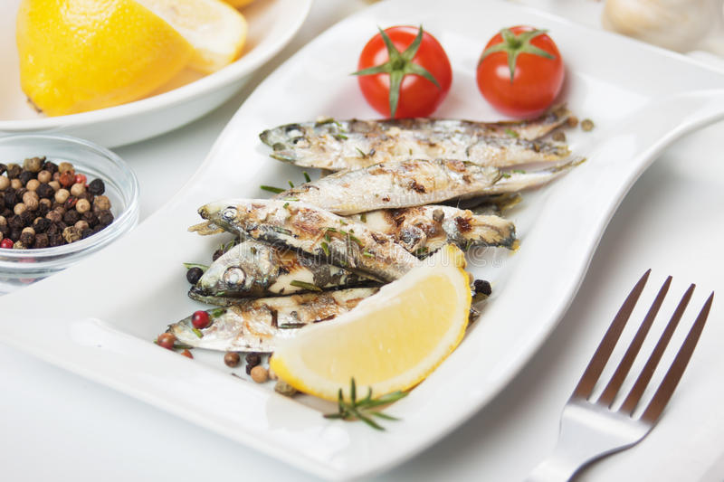 Grilled sardine fish. With lemon, herbs and cherry tomato royalty free stock photography