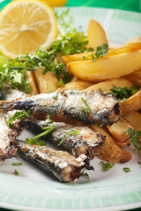 Grilled sardine fish with potato wedges. Grilled sardine fish with fried potato wedges royalty free stock images