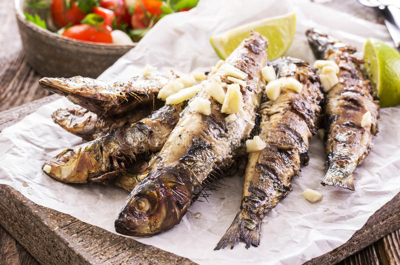 Grilled Sardines. As closeup on a stone tray stock photography