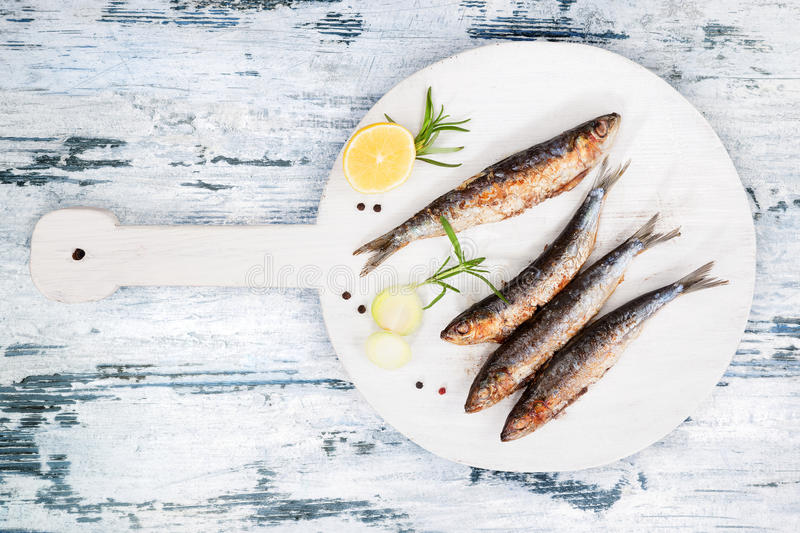 Grilled sardines. Delicious grilled sardines on wooden kitchen board on white and blue wooden textured background. Culinary seafood eating stock photography