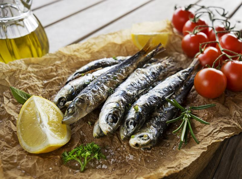 Grilled Sardines with herbs and lemon. Fried sardines with lemon and salad close up stock images