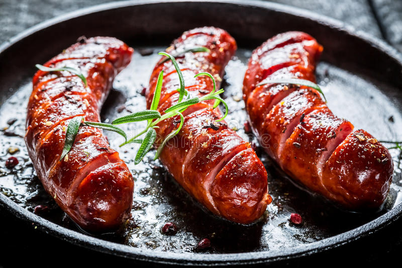Grilled sausage with fresh rosemary on hot barbecue dish. On burnt table stock photography