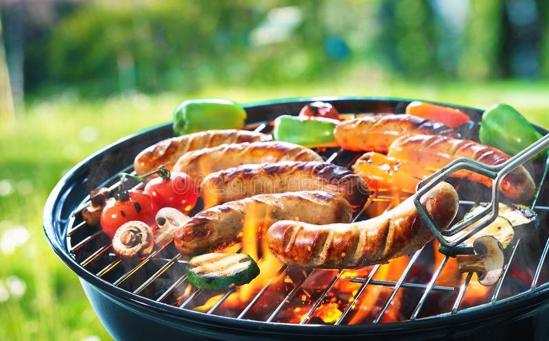 Grilled sausage on the flaming grill royalty free stock image