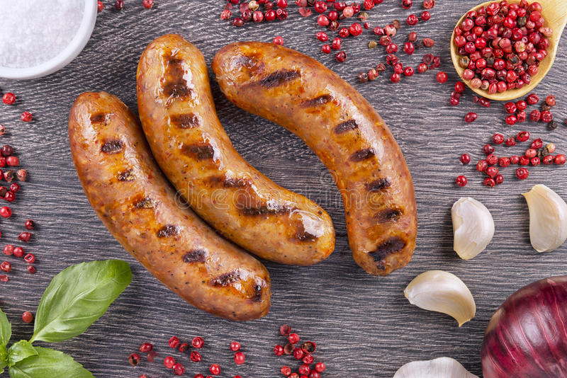Grilled sausage. With spices on a dark wooden background stock photography