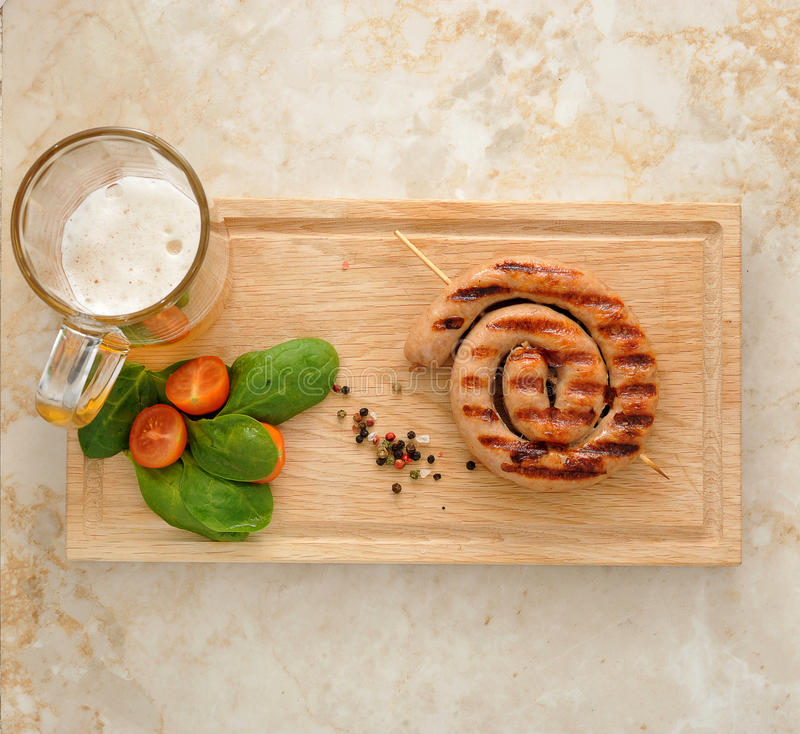 Grilled sausage in a spiral - pork sausage on a wooden skewer, m. Ug of beer, mashed potatoes, spinach and tomatoes. top view royalty free stock photos