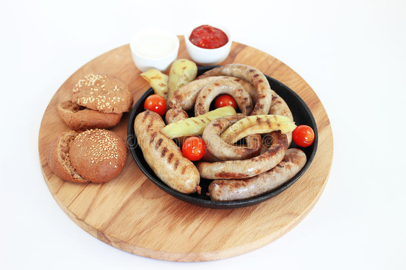 Grilled sausage on a wooden board with sauce, isolation stock photo