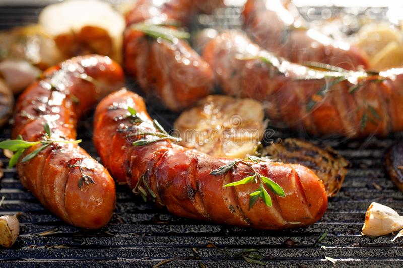 Grilled sausages with the addition of herbs and vegetables on the grill plate, outdoors, close-up. stock image