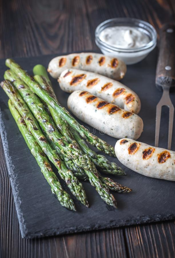 Grilled sausages with asparagus and creamy garlic sauce stock photography