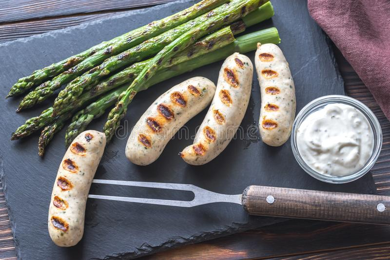 Grilled sausages with asparagus and creamy garlic sauce royalty free stock image