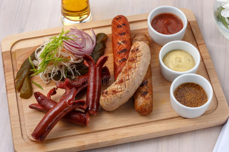 Grilled sausages for beer on a board stock photo