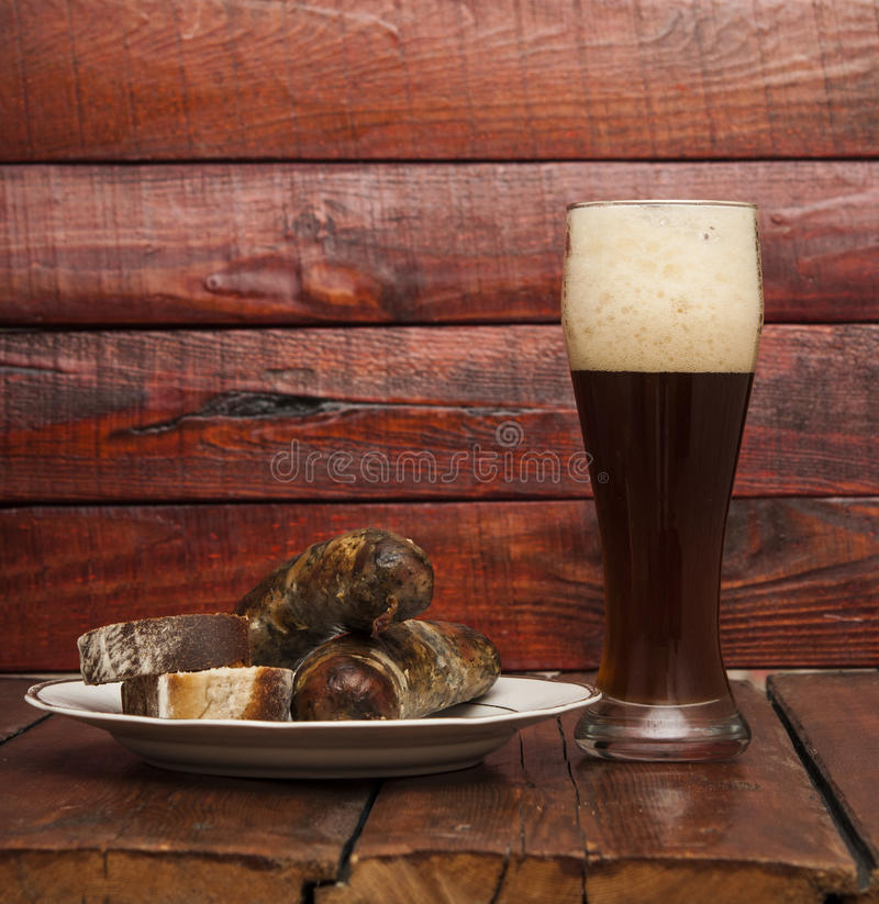 Grilled sausages. Beer and grill sausage on wooden background royalty free stock photo