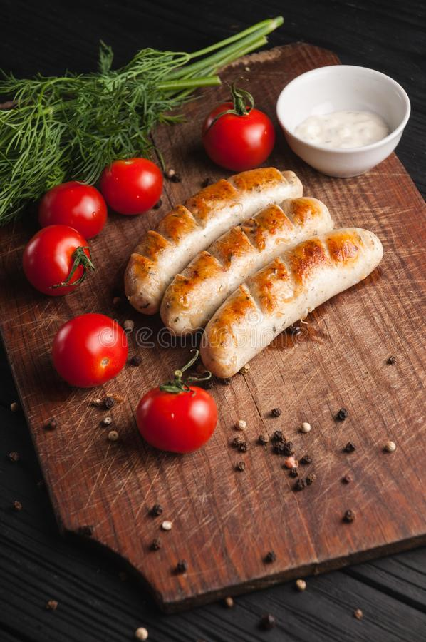 Grilled sausages grilled on a brown wooden board on a wooden background, six cherry tomatoes, greens, parsley dill, pepper, sauce royalty free stock images