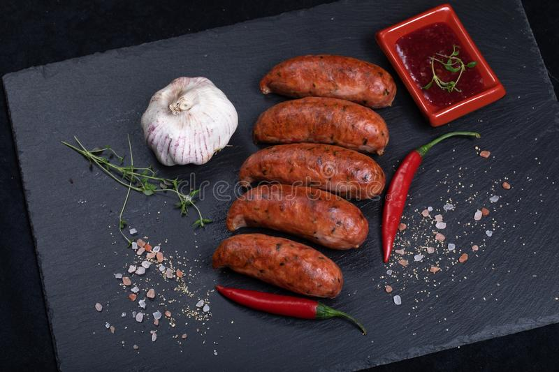 Grilled sausages with chilli peppers. Close up of grilled sausages on black stone plate with garlic, chilli and sause royalty free stock photography